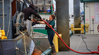 image describes someone fueling or working on a vehicle at one of Petro Marine's fueling stations around Alaska. She is a technician and possibly a machine operator.